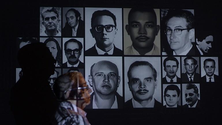 Pastor Cláudio observa fotos de vitimas da ditadura